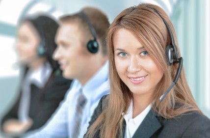 Service. Closeup of a call center employee with headset at workplace