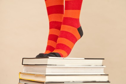feet in bright socks, standing on pile of books