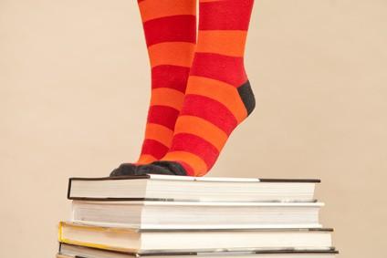 feet in bright socks, standing on pile of books