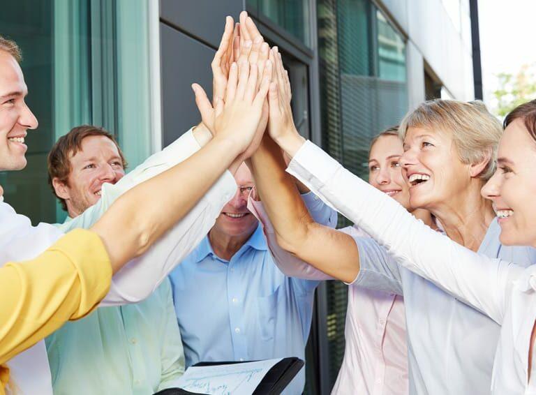 Jubelnde Geschäftsleute geben sich High Five mit den Händen vor dem Büro